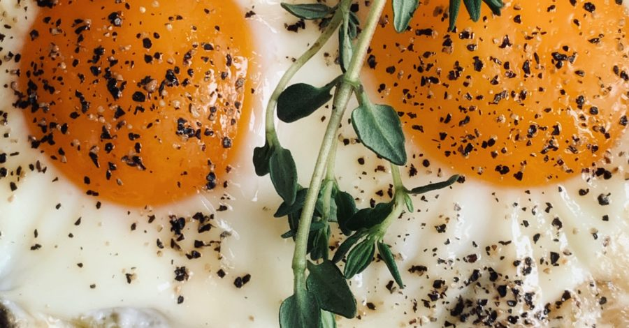 close up of egg yolks with sprig of thyme