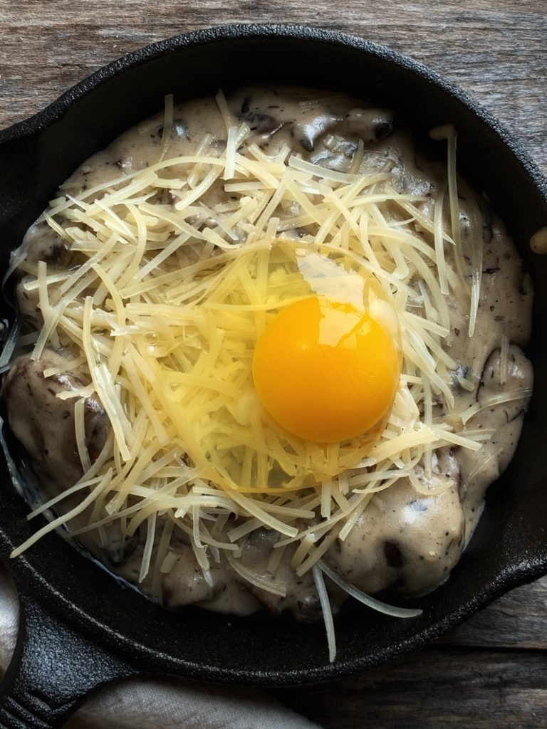 raw egg on bed of cheese